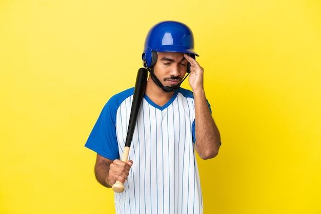 Jovem latino colombiano jogando beisebol isolado em um fundo amarelo com dor de cabeça
