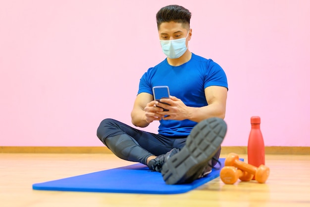 Jovem latino com máscara protetora, relaxado, usando telefone celular após o treino na academia durante a pandemia de novo normal.