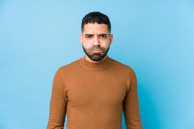 Jovem latino contra um fundo azul isolado bochechas de golpes, tem expressão cansada. conceito de expressão facial.