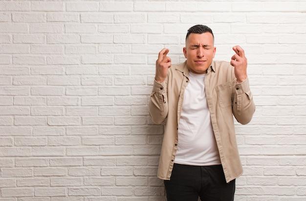 Jovem latino cruzando os dedos para ter sorte