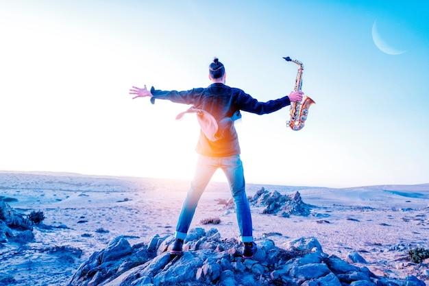 Jovem latino de braços abertos segurando um saxofone com uma das mãos no deserto do atacama chile