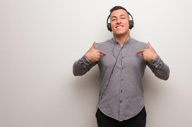 Jovem latino ouvindo música surpreso, se sente bem sucedido e próspero