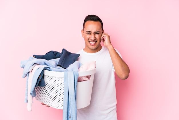 Jovem latino pegando roupas sujas isoladas, cobrindo as orelhas com as mãos.
