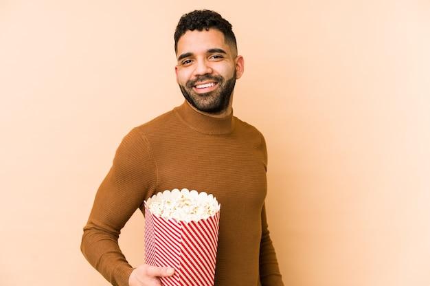 Jovem latino segurando um balde de pipoca olhando de lado