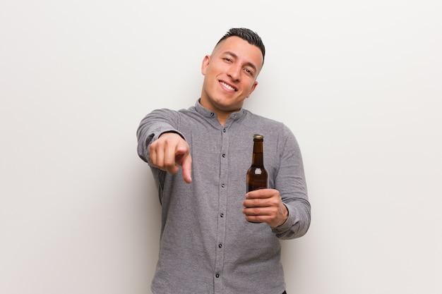 Jovem latino segurando uma cerveja, alegre e sorridente, apontando para a frente