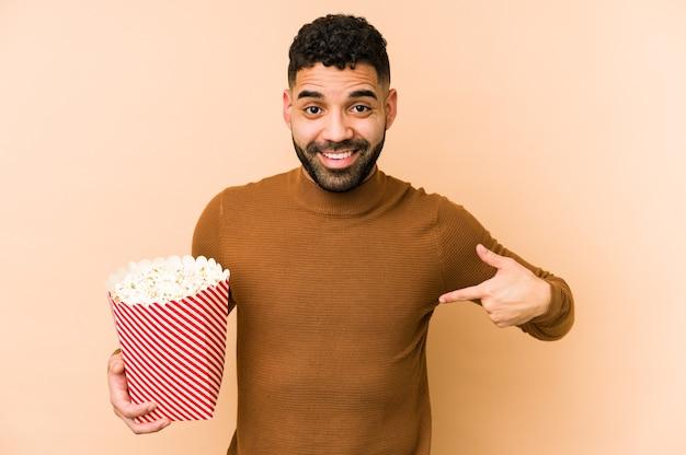 Jovem latino segurando uma pessoa isolada de pipoca apontando com a mão para um espaço de cópia de camisa, orgulhoso e confiante