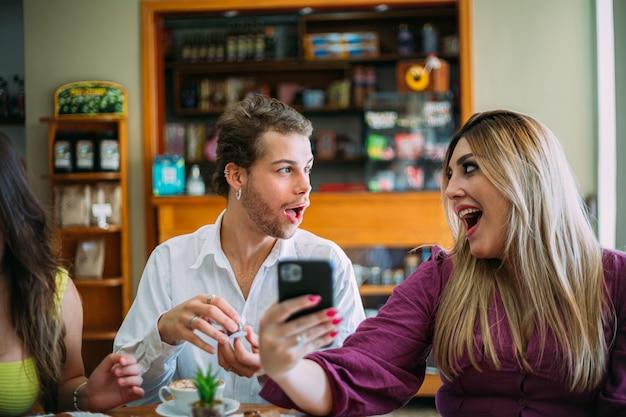 Jovem latino surpreendeu amigos gritando no café de comida de rua brilhante retrô usando telefone celular.