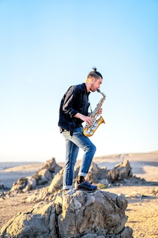 Jovem latino tocando saxofone no deserto do atacama, no chile