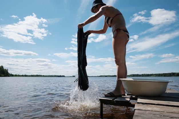 Jovem lava roupas à mão no lago. lavar as roupas na natureza. lavando roupas no lago.