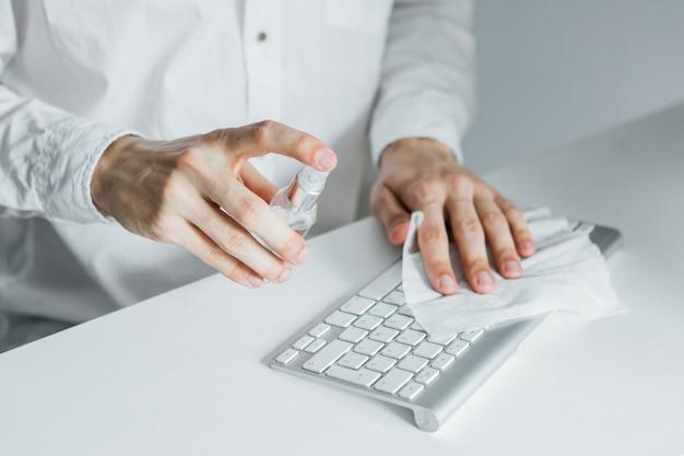 Jovem lava teclado com um anti-séptico em sua mesa. trabalhador de escritório
