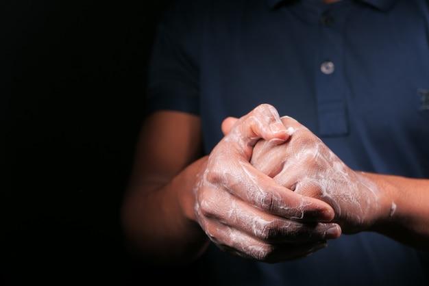 Jovem, lavando as mãos com água morna e sabão.