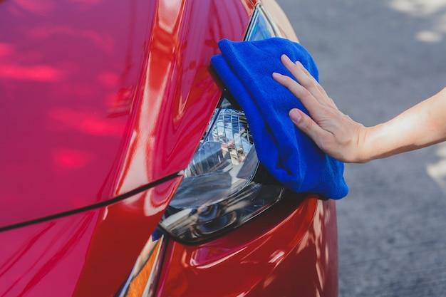 Jovem, lavando, e, limpando um carro, em, a, ao ar livre