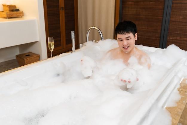 Jovem lavando o corpo e jogando espuma de espuma na banheira