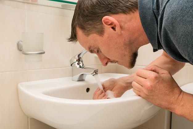 Jovem lavando o rosto. banheiro.