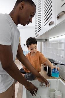 Jovem lavando pratos com seu filho