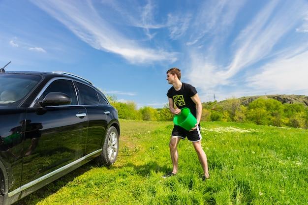 Jovem lavando um veículo preto de luxo em um campo verde relvado em um dia ensolarado com céu azul, jogando um balde de água na lateral do carro