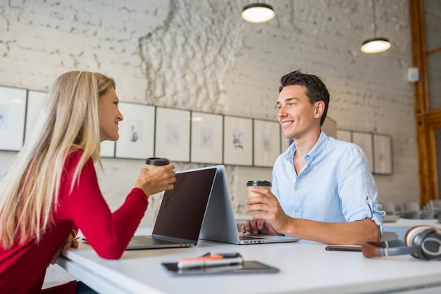 Jovem legal e mulher sentada à mesa, cara a cara, trabalhando em um laptop em um escritório colaborativo