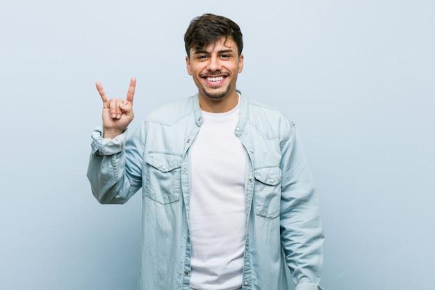 Jovem legal hispânico mostrando um gesto de chifres como uma revolução.