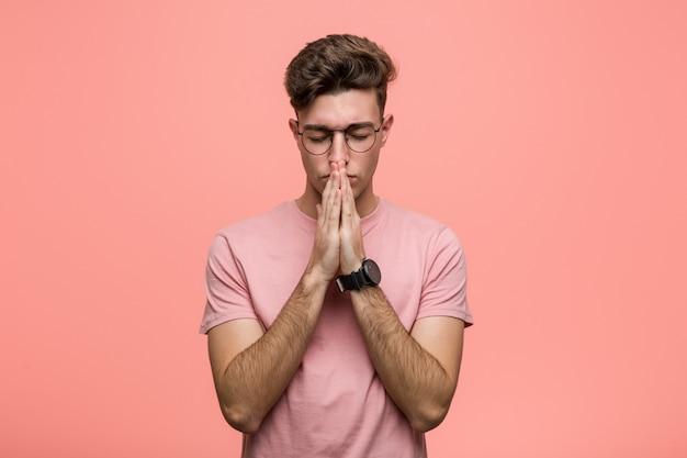 Jovem legal homem caucasiano de mãos dadas em rezar perto da boca, sente-se confiante.