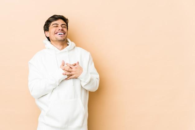 Jovem legal rindo mantendo as mãos no coração, o conceito de felicidade.