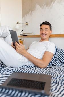 Jovem legal sorridente com roupa de pijama casual sentado na cama pela manhã segurando um tablet, freelancer em casa