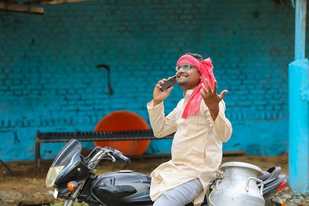 Jovem leiteiro indiano falando no smartphone