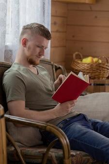 Jovem lendo livro com capa vermelha em um banco de vime em uma casa de madeira do campo