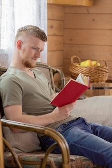 Jovem lendo livro com capa vermelha no banco de vime na casa de campo