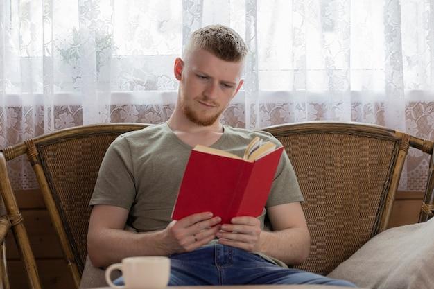 Jovem lendo livro com capa vermelha no banco de vime na casa de madeira