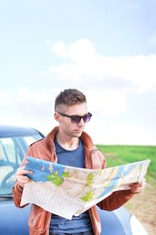 Jovem lendo mapa rodoviário perto de seu carro