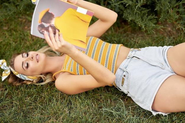 Jovem lendo revista deitado na grama