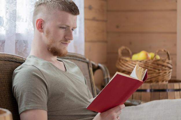 Jovem lendo um livro com capa vermelha em um banco de vime em uma casa de madeira rural contra o fundo de uma cesta de maçãs amarelas