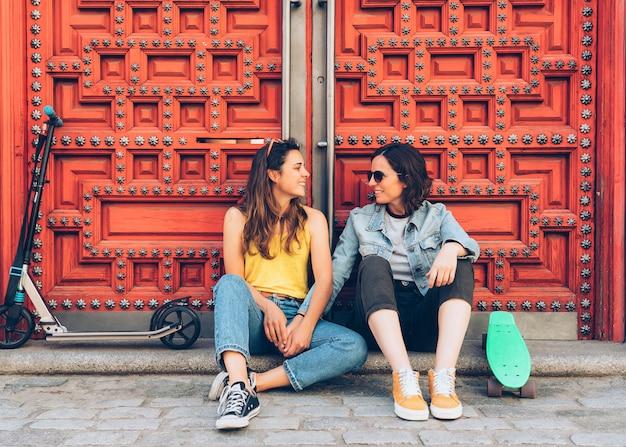 Jovem, lésbica, mulheres, par, falando, e, segurar passa, em, um, porta vermelha