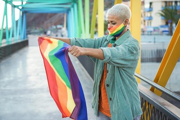 Jovem lésbica segurando bandeira gay lgbt de arco-íris - foco no rosto