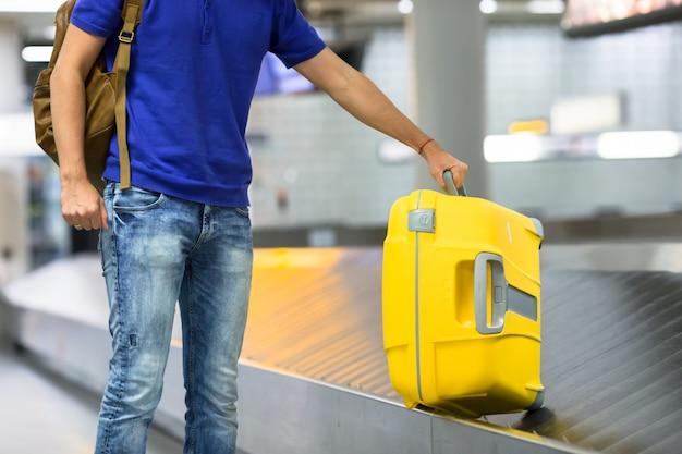 Jovem, levando a bagagem do cinto no aeroporto