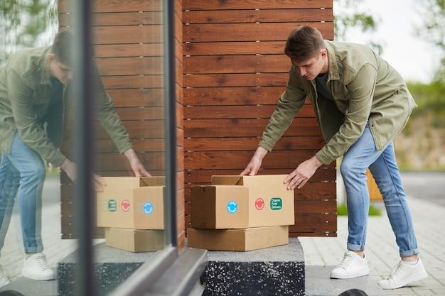 Jovem levando seus pacotes diante da porta do lado de fora, pedindo entrega de comida