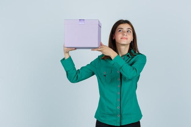 Jovem, levantando a caixa de presente acima do ombro na blusa verde, calça preta e parecendo feliz, vista frontal.