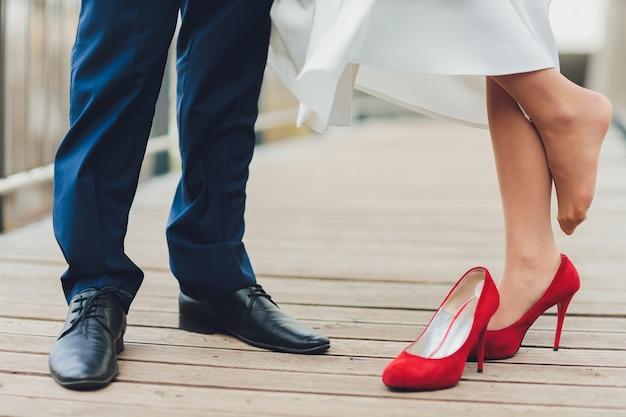 Jovem, levantando a noiva ao ar livre, close-up da parte inferior dos corpos.