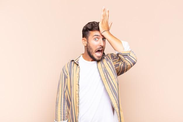 Jovem levantando a palma da mão na testa pensando opa, depois de cometer um erro estúpido ou lembrar, sentindo-se bobo
