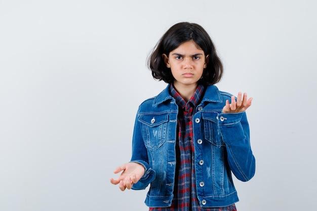 Jovem, levantando as mãos de forma questionadora em camisa quadrada e jaqueta jeans e olhando perplexa, vista frontal.