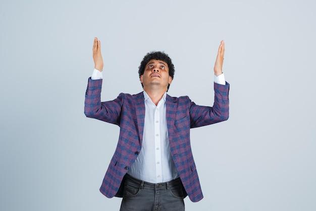 Jovem levantando as mãos enquanto olha para cima na camisa, jaqueta, calça e parecendo esperançoso, vista frontal.