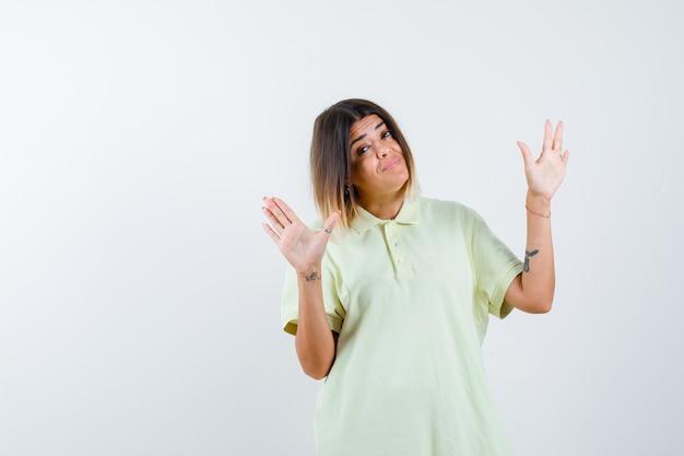 Jovem, levantando as palmas das mãos em um gesto de rendição em t-shirt e olhando feliz, vista frontal.