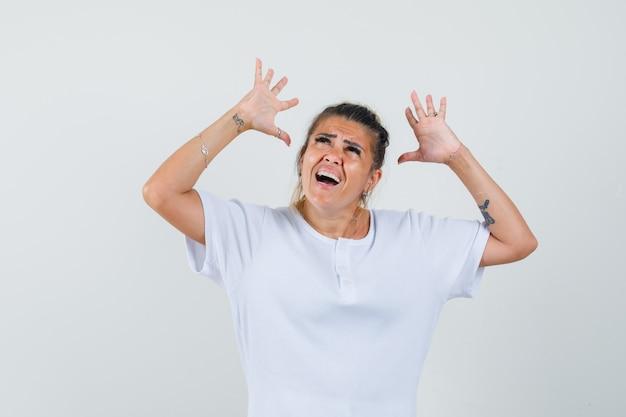 Jovem levantando os braços em uma camiseta e parecendo preocupada