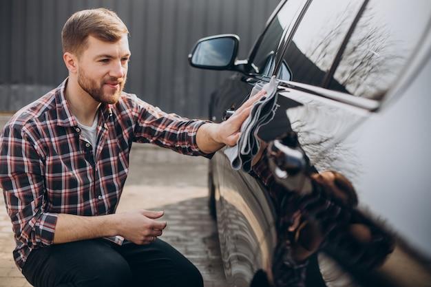 Jovem limpando o carro após a lavagem