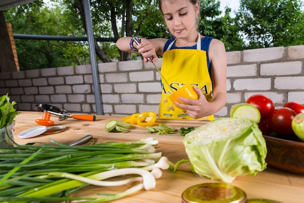 Jovem, limpando um pimentão, tirando a casca com uma faca enquanto está em uma mesa preparando legumes frescos