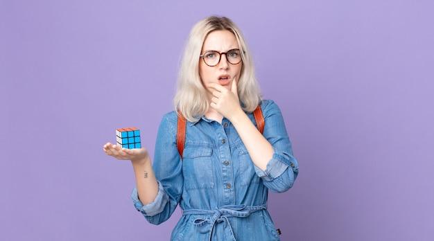Jovem, linda, albina, com boca e olhos bem abertos e mão no queixo, resolvendo um jogo de inteligência