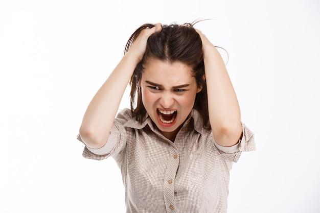 Jovem linda brava louca businessgirl morena segurando a cabeça e gritando olhando para baixo sobre parede branca