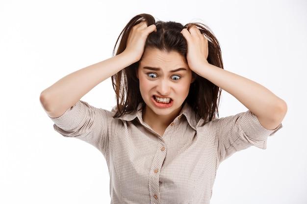 Jovem linda brava louca businessgirl morena segurando a cabeça e gritando olhando para longe sobre parede branca