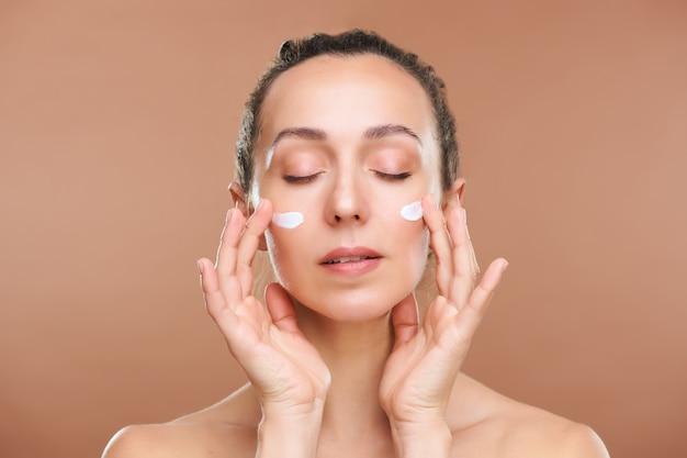 Jovem linda com os olhos fechados, aplicando creme facial rejuvenescedor nas bochechas enquanto cuida de sua pele pela manhã