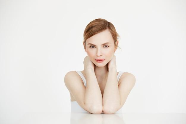 Jovem linda com pele limpa perfeita, sorrindo, sentado à mesa. spa de beleza e cosmetologia.